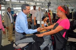 Fidel Santana saluda a una empleada de zona franca en Navarrete.