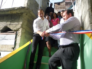 Román Batista realiza el corte de cinta, a su lado, el alcalde de SDE, Juan de los Santos.